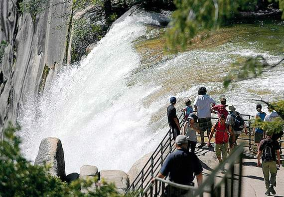 Hikers reach the vista point at Vernal Fall after hiking the Mist Trail Wednesday, July 20, 2011, a day after three visitors reportedly slipped into the Merced River above Vernal Fall in Yosemite National Park, Calf. The three young tourists are presumed dead; rescuers continued searching for their bodies Wednesday. (AP Photo/The Fresno Bee, Eric Paul Zamora)