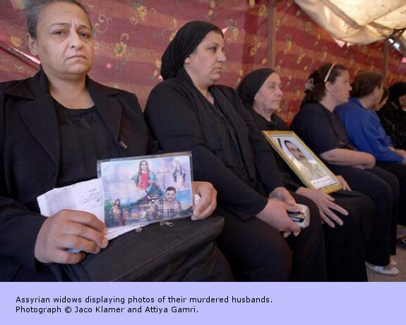 Assyrian widows displaying photos of their murdered husbands.