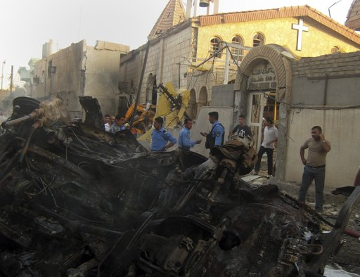 Iraqis inspect the site of an early morning car bomb attack in front of a Church in Kirkuk, 290 kilometers (180 miles) north of Baghdad, Iraq, Tuesday, Aug. 2, 2011. Scores of people were injured in the attack, police said. (AP Photo/Emad Matti)