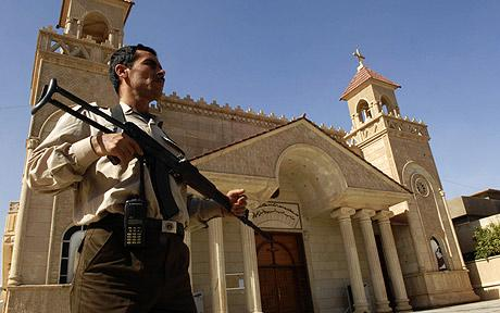 An armed man outside a cathedral in Kirkuk, Iraq. (Photo: AP)