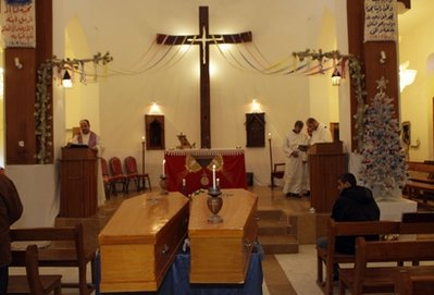Coffins of slain Christians, Fawzi Rahim, 76, left, and Janet Mekha, 78, right, are seen during their funeral Mass at St. George Chaldean Church in Baghdad, Iraq, Friday, Dec. 31, 2010. Militants in Iraq have attacked at least four Christian homes with a combination of grenades and bombs, killing and wounding a few people and sending fear into the country's already terrified tiny Christian community, police said.