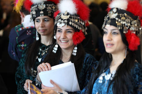 Rounza Gorges (from left), Kathy Polus and Sarah Adam welcome guests Sunday to the kickoff Coming Together In Skokie event at Niles West High School. This year's edition celebrates Assyrian Culture. | Jerry Daliege~for Sun-Times Media
